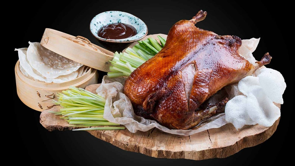 Beautifully roasted Peking Duck topped with orange slices and green onion.