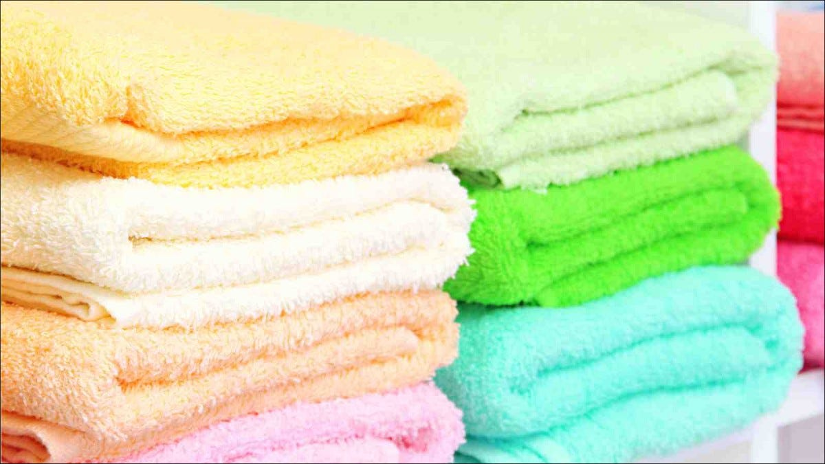 colorful towels on shelves in bathroom