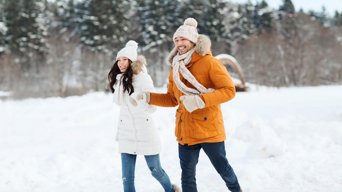 A couple dressed in winter coats and hats holding hands and walking in the snow.