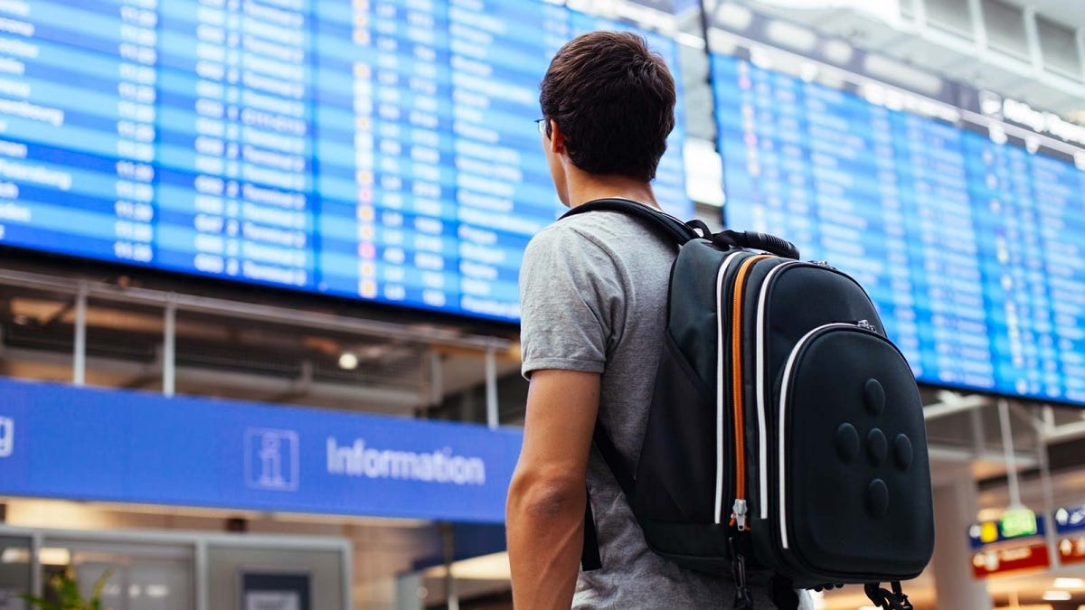 A man wearing a backpack, studying the departures board at the airport.