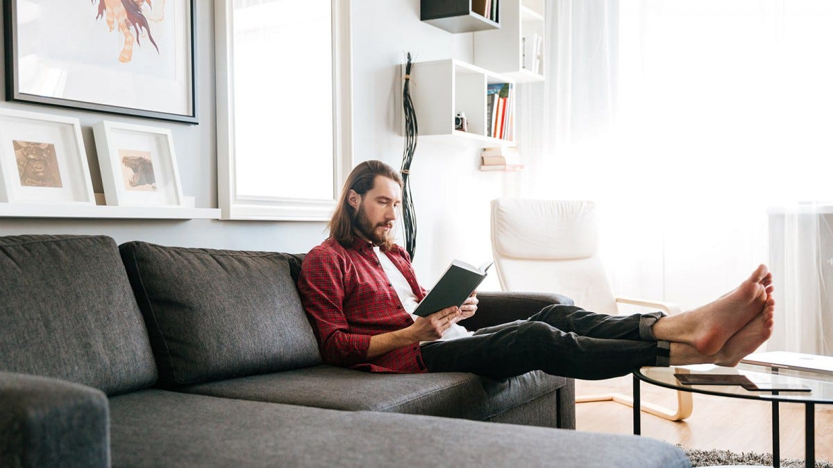 A man sitting on a sectional sofa with his feet up on a coffee table, reading a book.