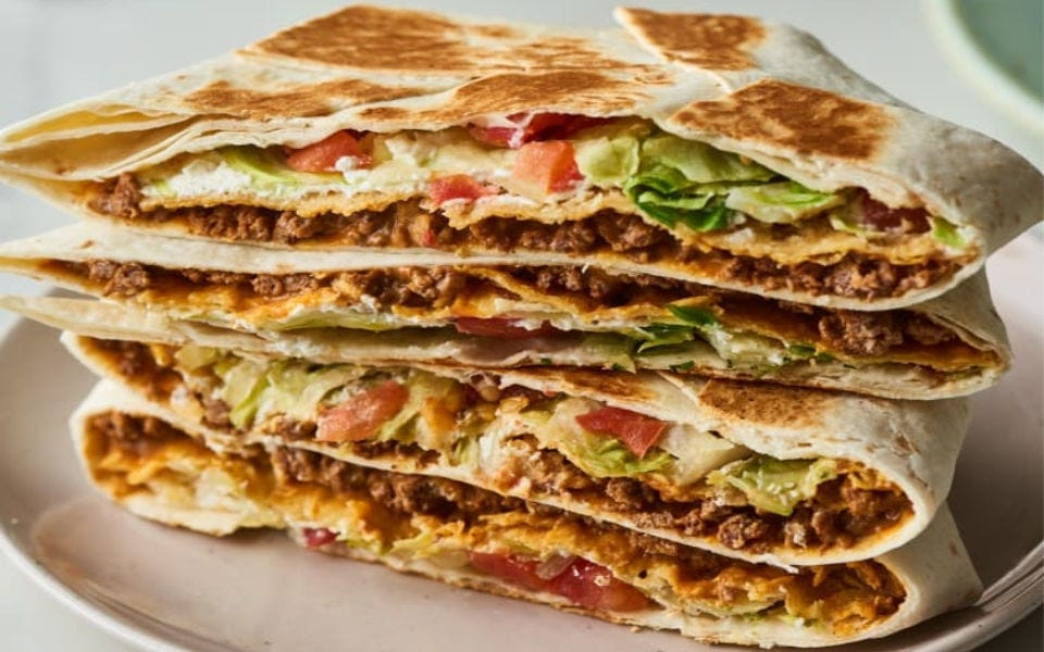 Two Taco Bell-style crunchwrap supremes sliced and stacked on top of each other.