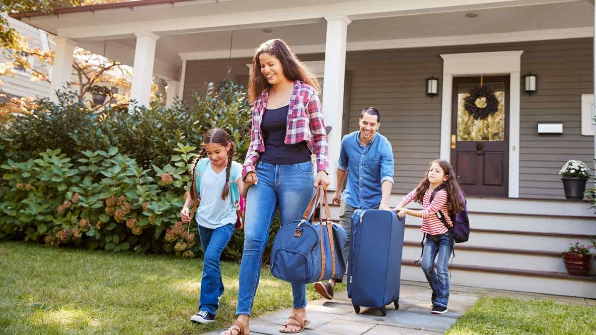 Family, with luggage in hand, leaving a beautiful house with a wide front porch