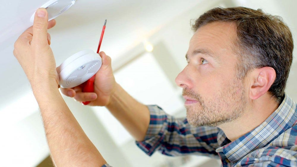 A man installing a new smoke detector.