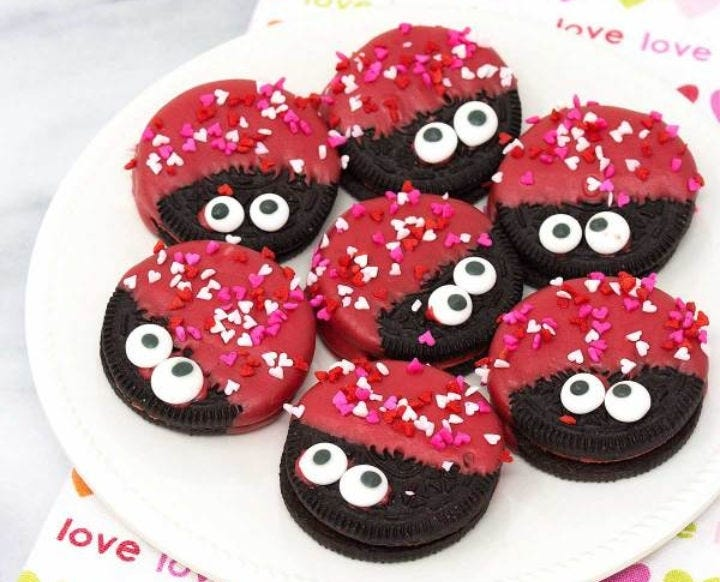 Seven decorated Love Bug Oreo cookies on a white plate.