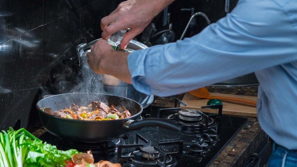 A man grinding sea salt onto some meat and veggies cooking in a skillet.