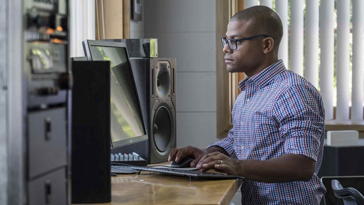 man standing at his computer work station