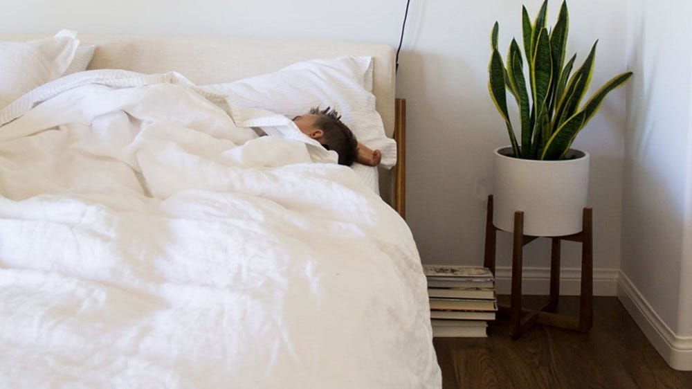 Someone sleeping in a bed on white Brooklinen Linen Core Sheets.