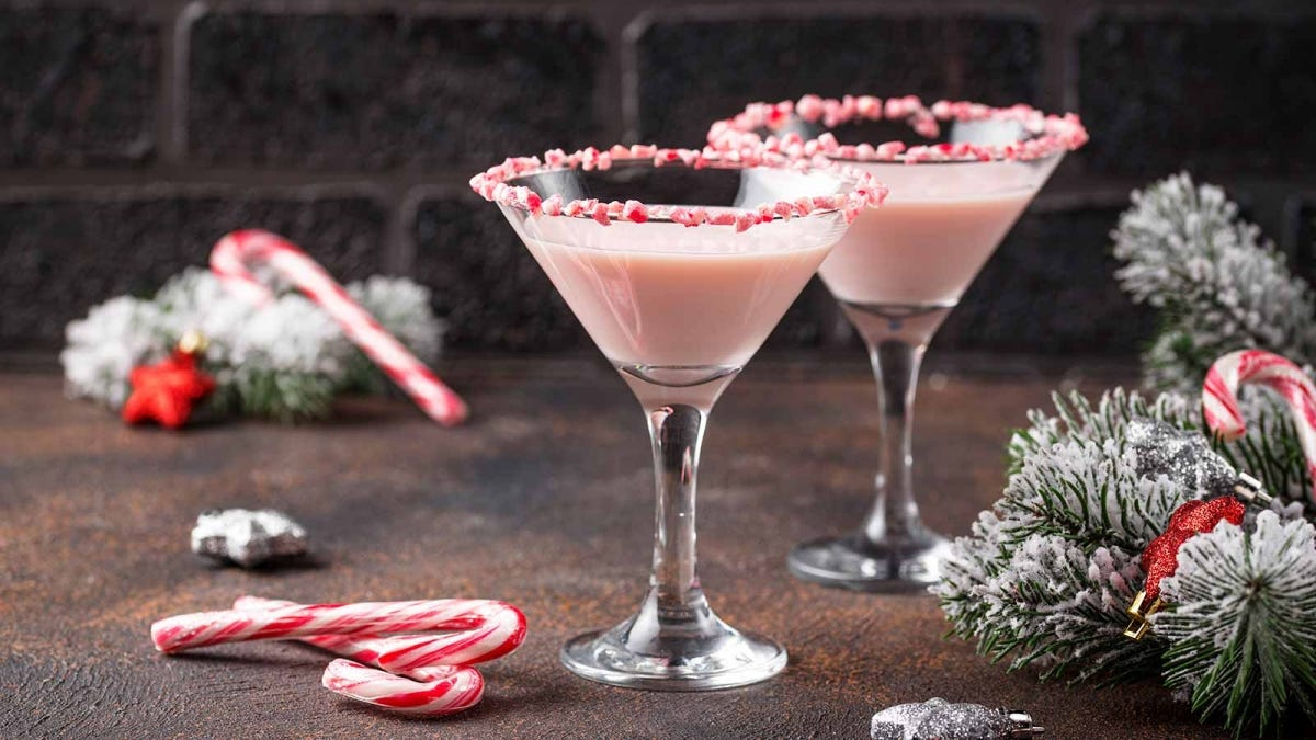 Two pink peppermint martinis sitting on a counter with candy canes and evergreen branches.