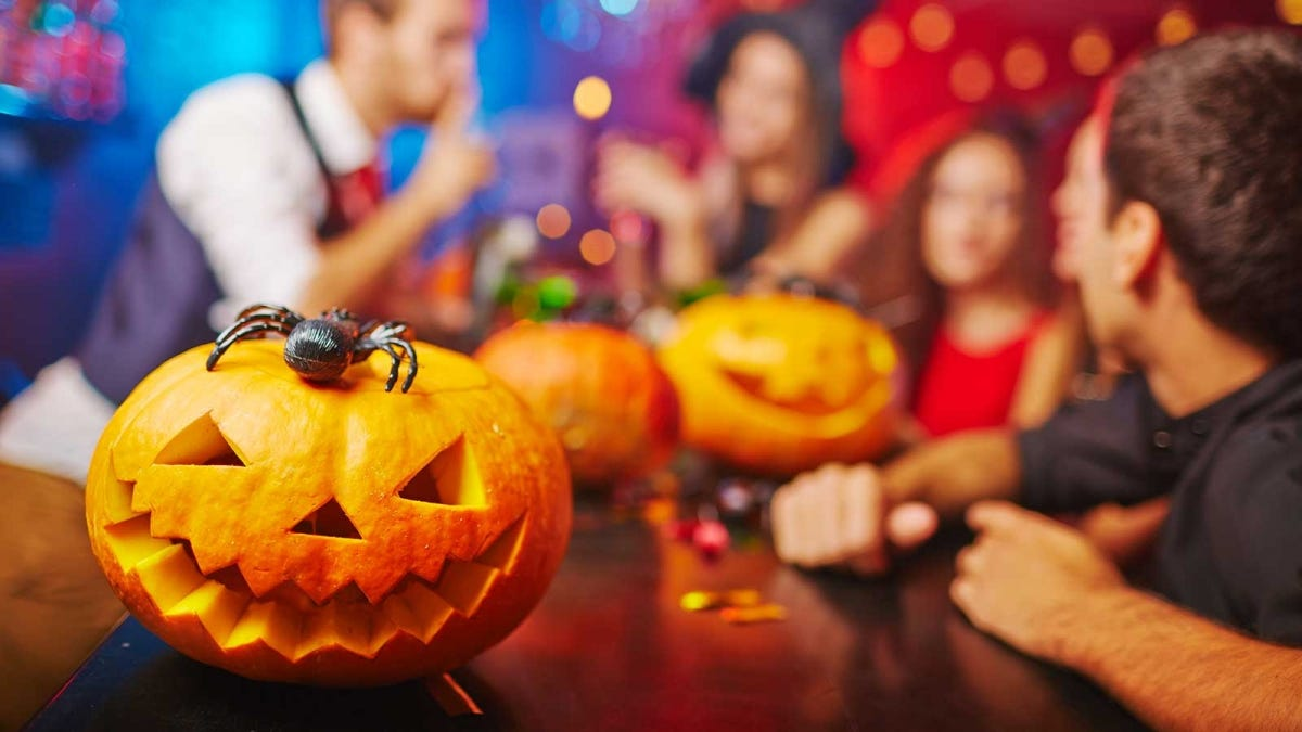 A jack-o'-lantern with a spider on top sitting on a bar with Halloween partiers in the background.