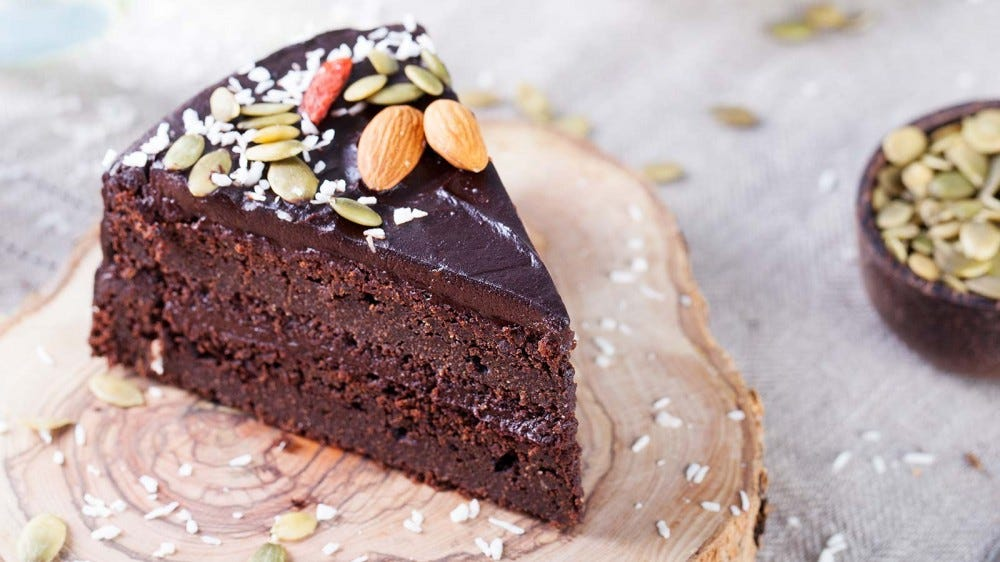A slice of vegan chocolate cake, sprinkled with nuts and resting on a rustic wood slab plate.