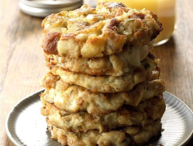 A stack of mashed potato and stuffing patties, with a glass of orange juice in the background.