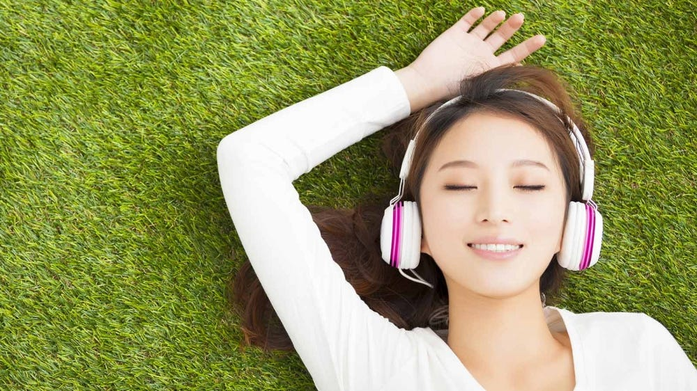 A woman lying on the grass listening to headphones.