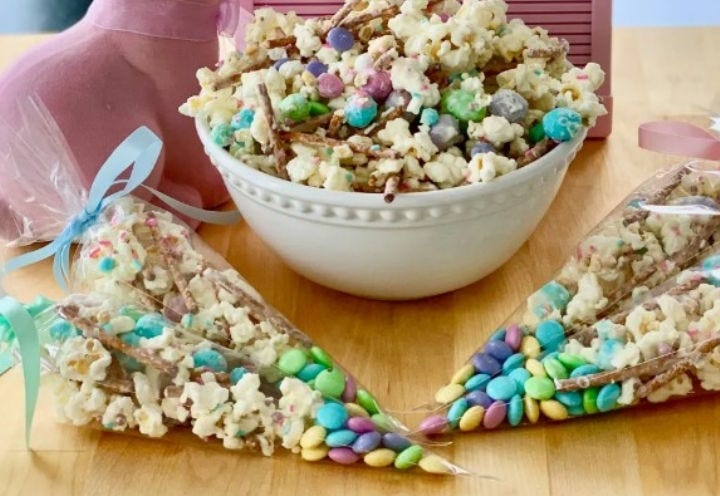 A large bowl full of bunny bait surrounded by four decorated baggies of it.