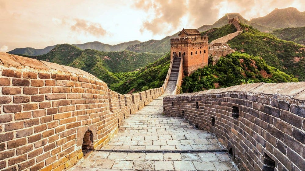 A photo of the Great Wall of China, reaching out towards the horizon over tree-covered mountains.