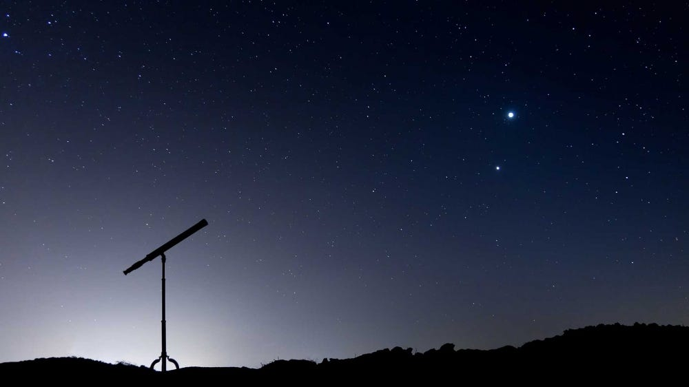 A backlit telescope against the night sky pointed at Jupiter and Venus.