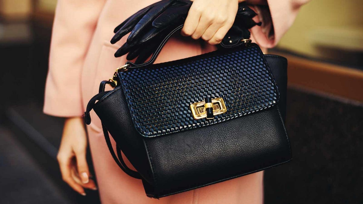 woman holding a black leather purse and matching black gloves