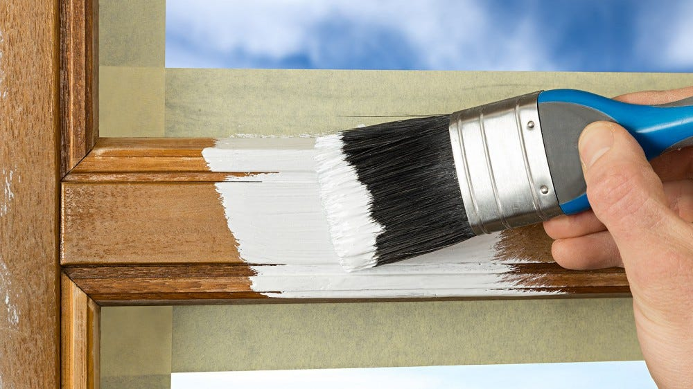 Someone painting a primer over wood window trim.