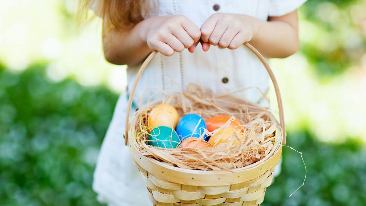 A little girl's hands holding a woven basket filled with natural grass and colorful Easter eggs resting on top.