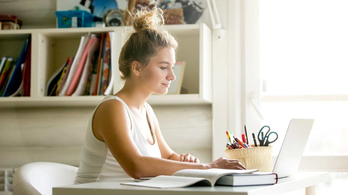 young woman studying at her desk in a sunny dorm room