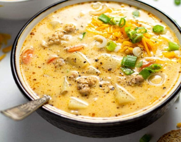 A bowl of sausage and potato beer cheese soup garnished with green onion and shredded cheddar.