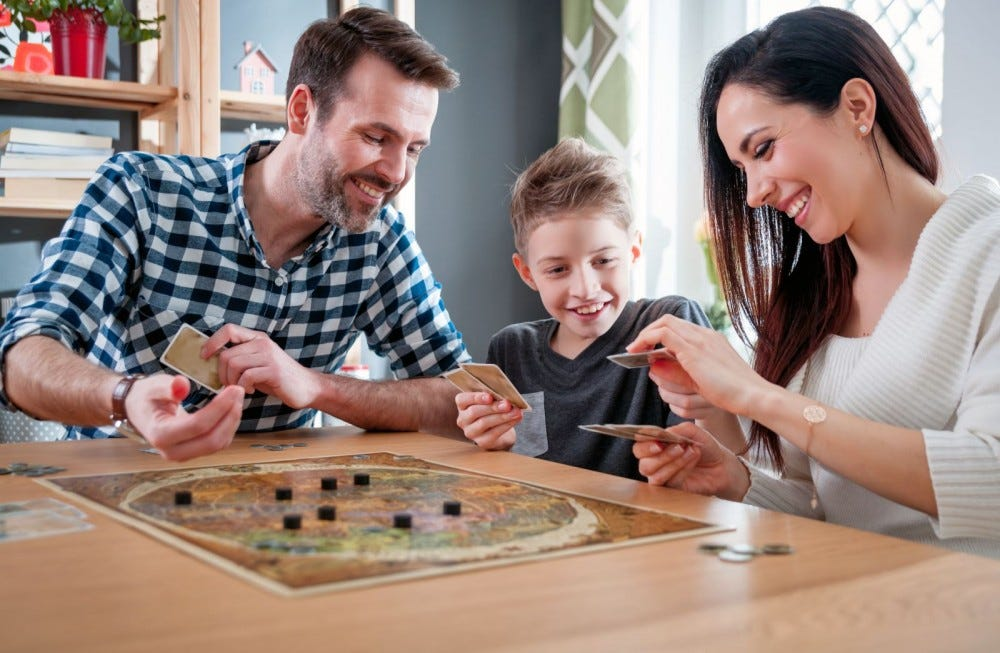 A mom, dad, and child playing a board game on family game night.