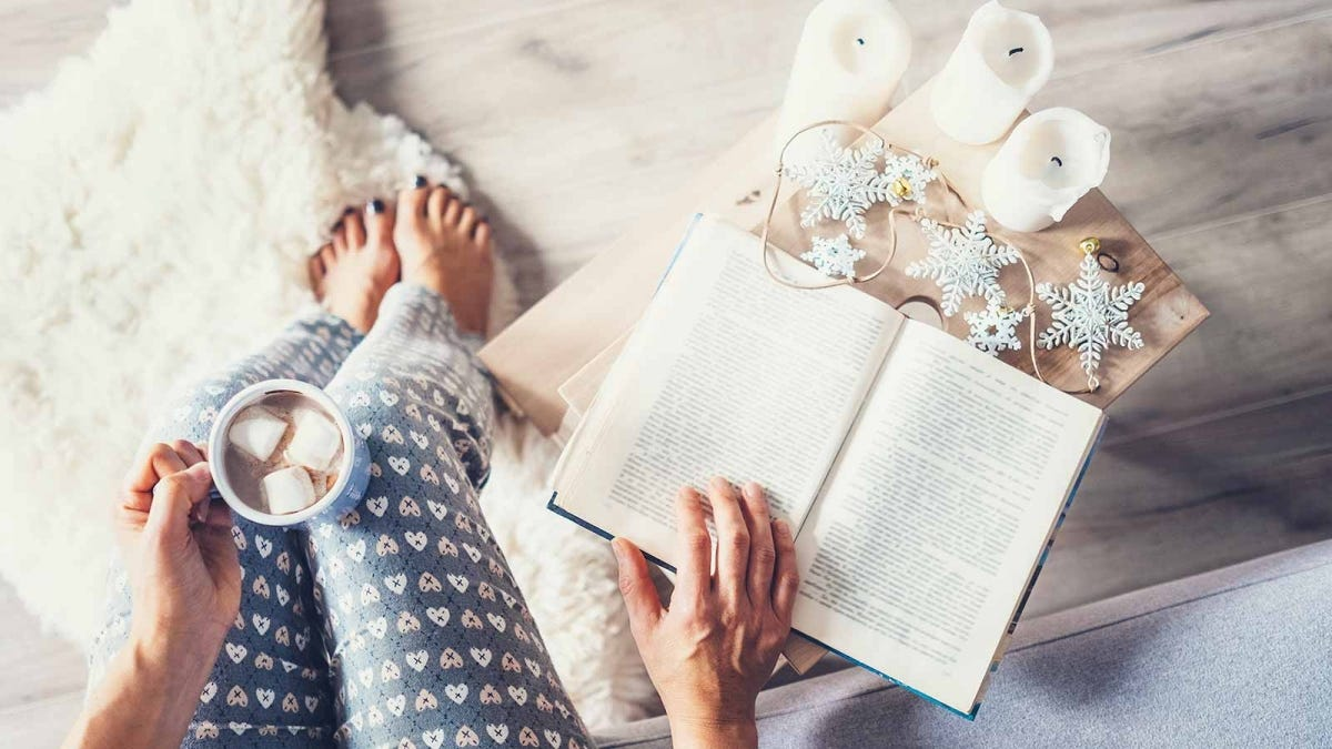 Woman reading a book and drinking hot chocolate in a cozy room.