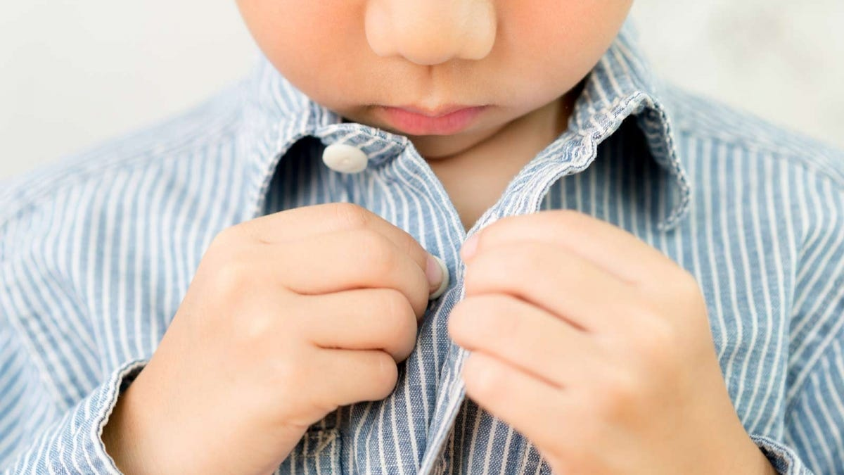Little boy practicing buttoning his shirt.
