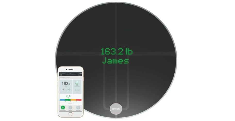 The black QardioBase2 smart scale with its companion app on a phone.