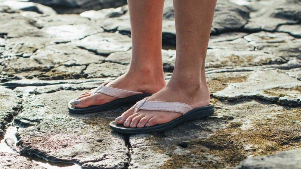 A woman wearing Olukai sandals, standing on mossy rocks.
