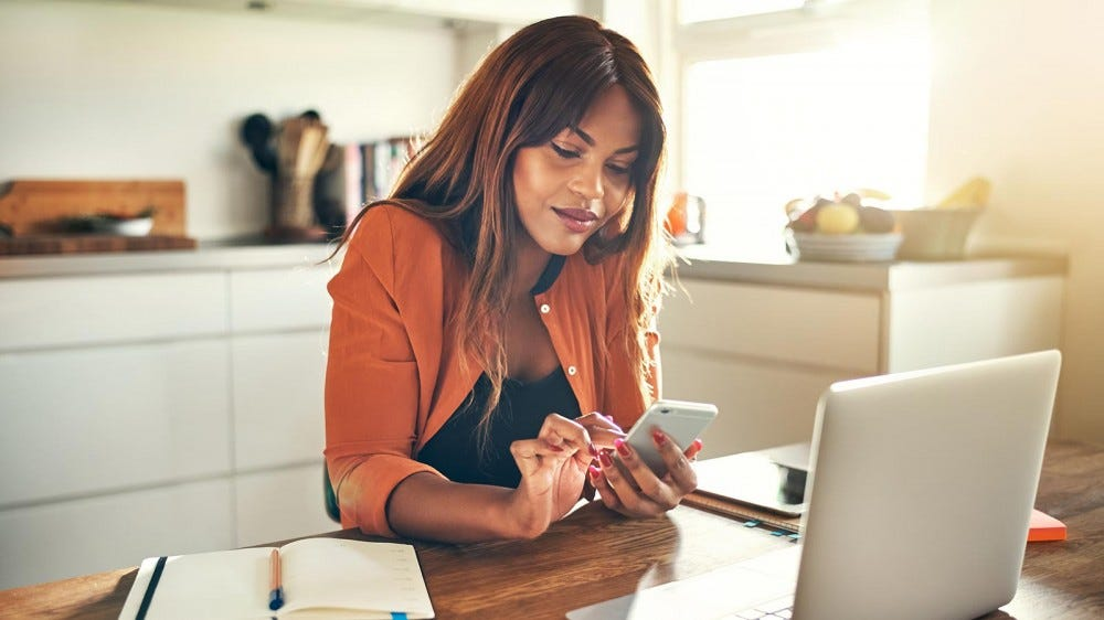 Woman working from home at her kitchen table, checking her to-do list on her phone.