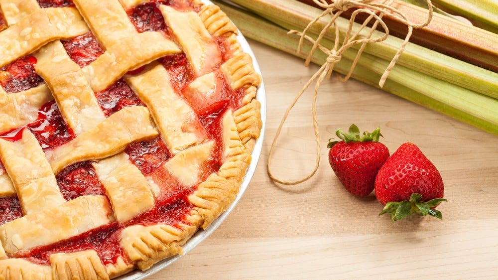 A strawberry rhubarb pie sitting on a table next to fresh strawberries and a bundle of rhubarb.