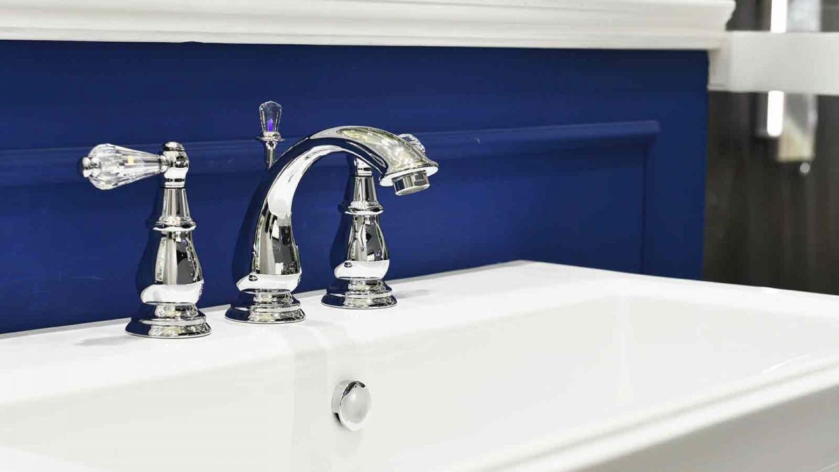 beautiful bathroom sink with chrome hardware and crystal knobs against a blue wall