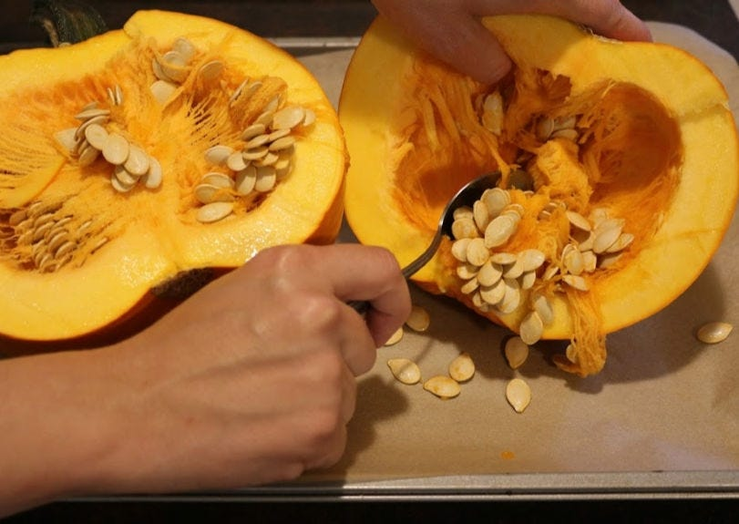 A hand using a spoon to scoop seeds out of a sugar pumpkin onto a baking sheet.