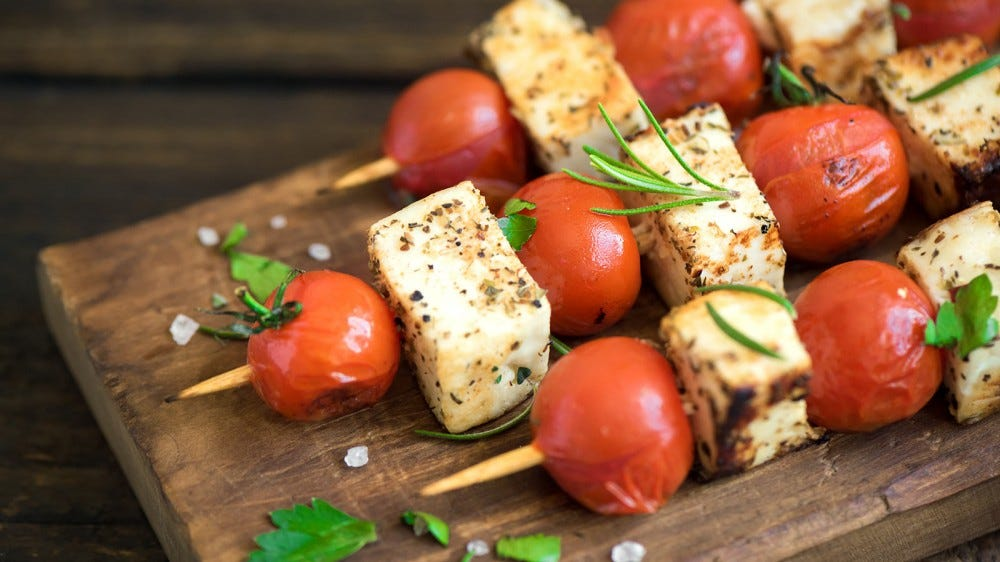 Vegetarian skewers with halloumi cheese and tomatoes on a chopping block.