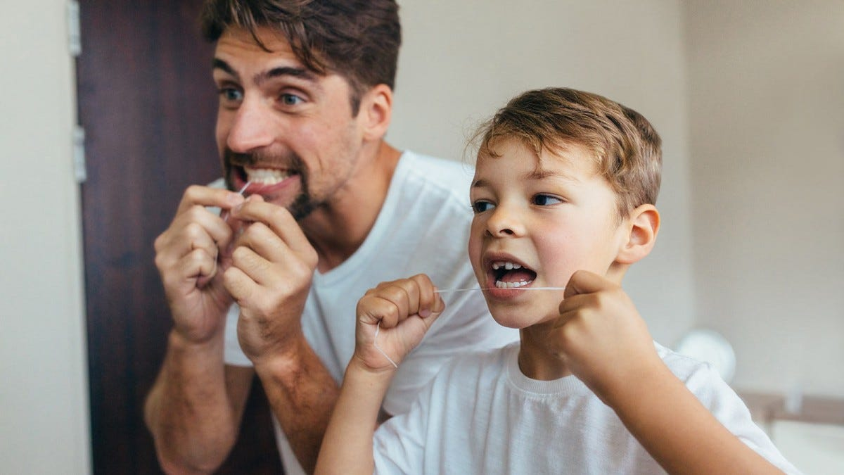 A father and son flossing in the bathroom.
