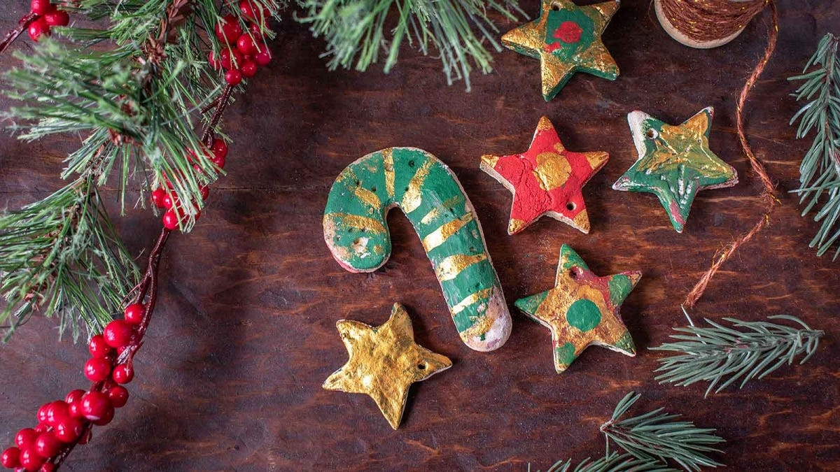 Salt dough ornaments laid out next to a Christmas tree.