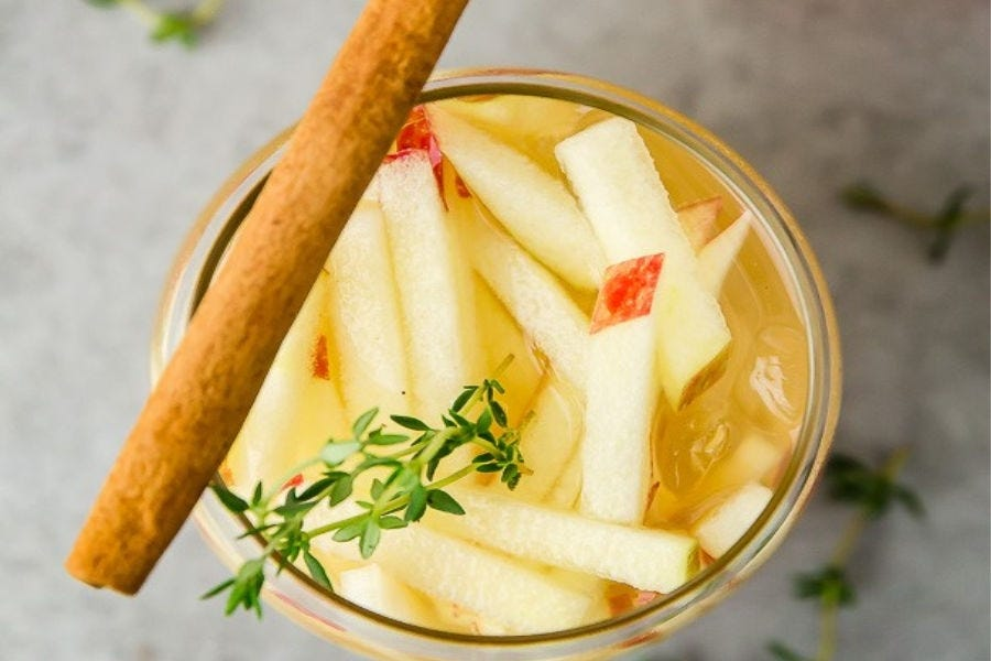 An Apple and Gin cocktail garnished with a cinnamon stick and matchstick sliced apples.
