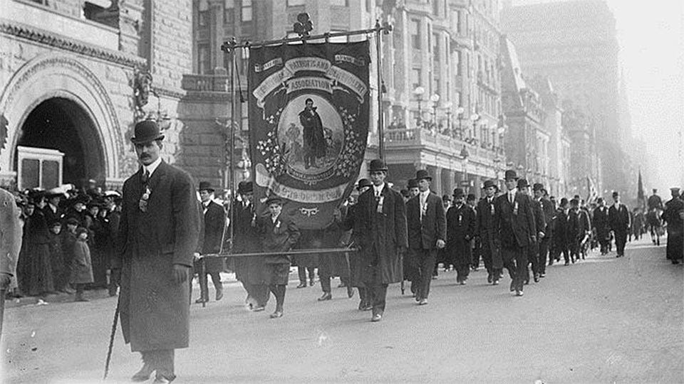 Men in suits and bowler hats carrying a banner of St. Patrick down a New York street in an early parade.