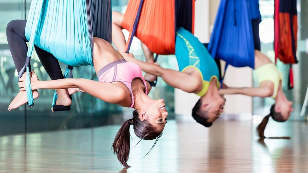 Two women and a man hanging upside down in aerial yoga harnesses.