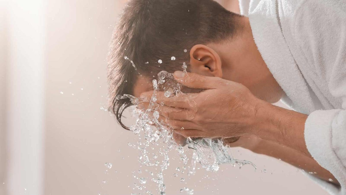 Man splashing cold water on his face to help calm himself