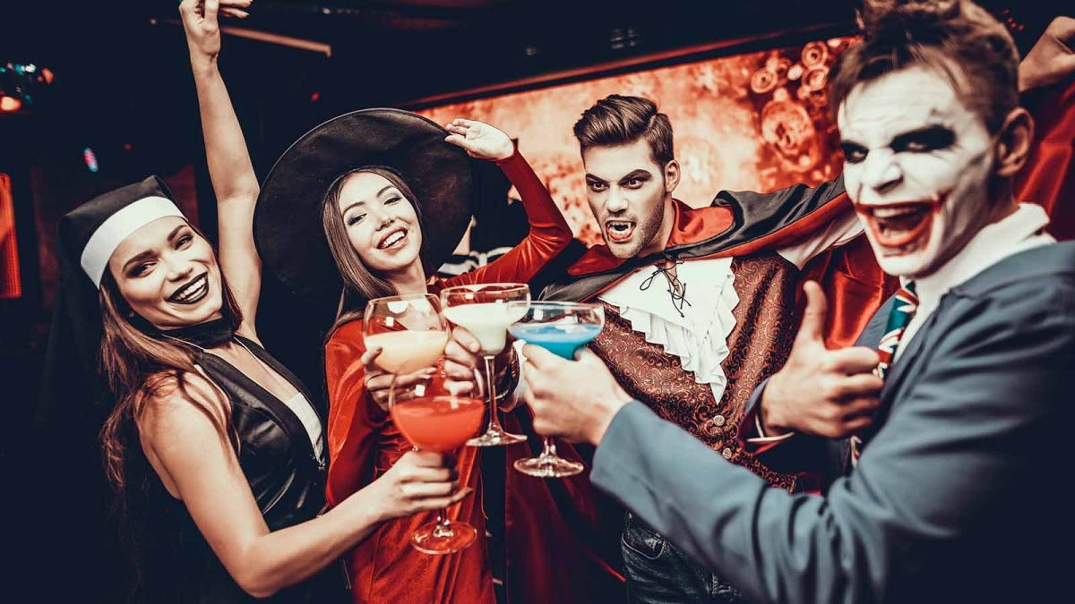 A group of people in Halloween costumes making a toast.