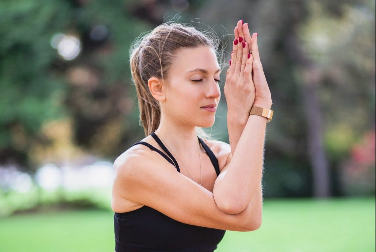 A woman meditating with her arms crossed and her eyes closed.
