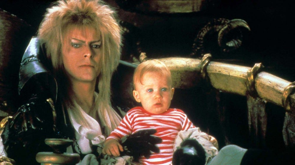 "Jareth (David Bowie) holding baby Toby in a scene from ""Labyrinth."""