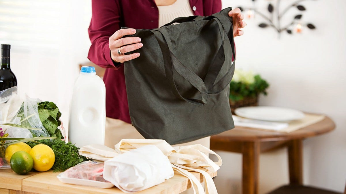 A woman's hands holding a cloth grocery sack next to a counter covered in unloaded groceries.
