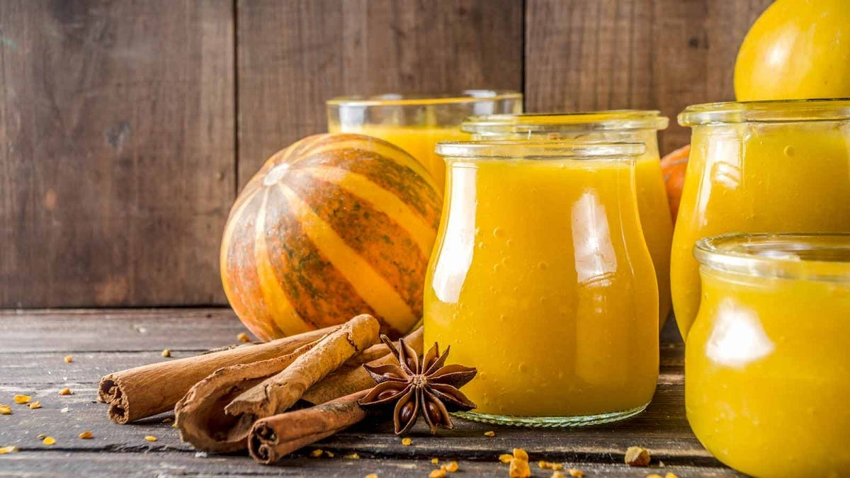 A pumpkin, jars of pureed pumpkin, and spices on a wooden table..