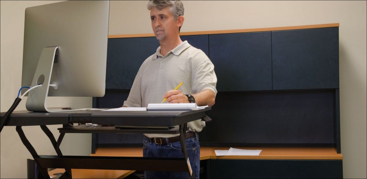 A man is working at a stand up desk in an office