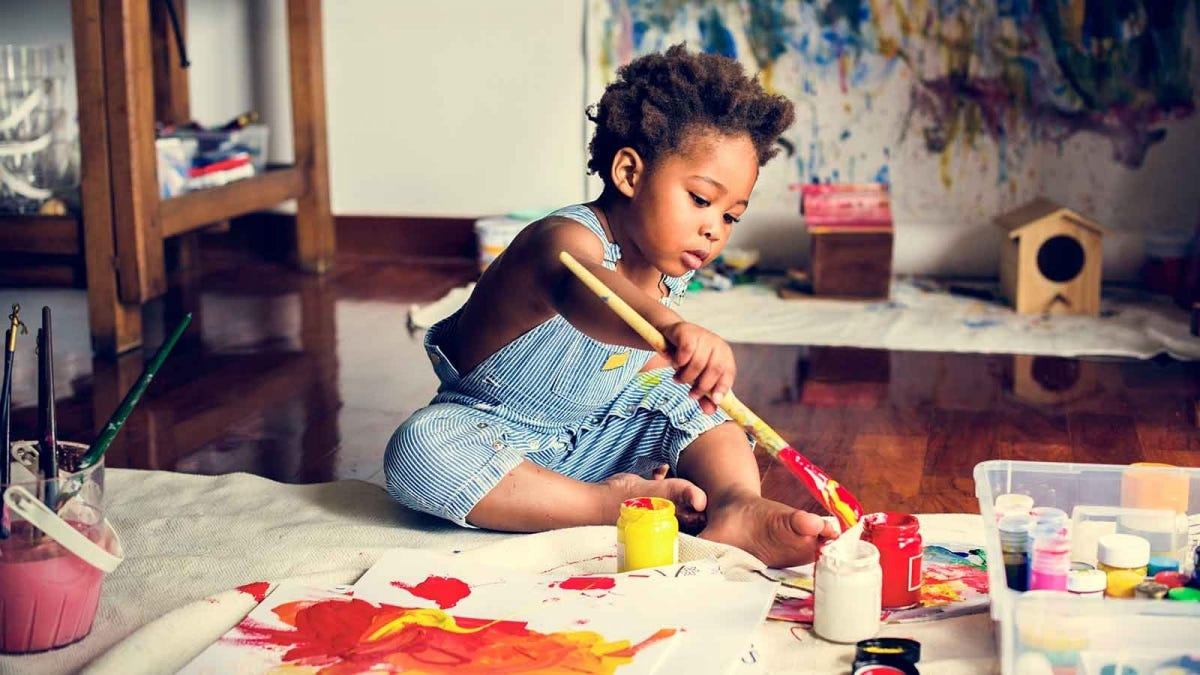 boy sitting on a table painting