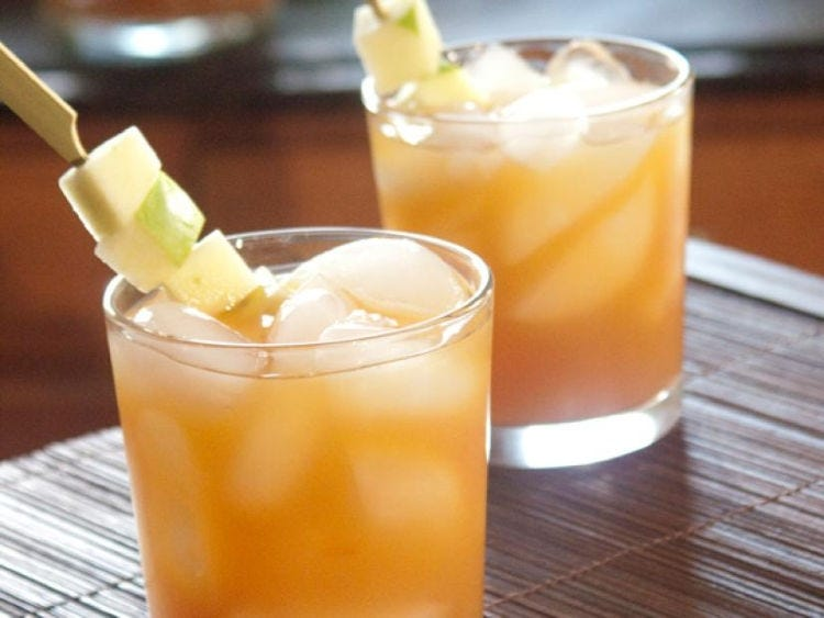 Two glasses with spiked apple cider on the rocks