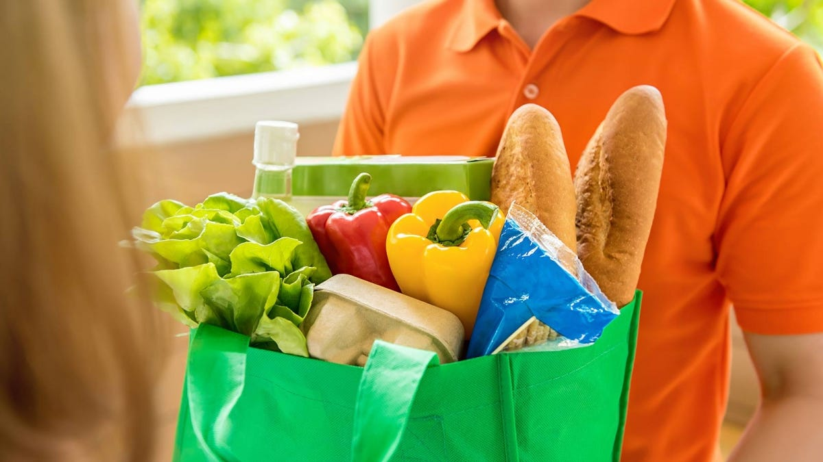 Man holding a reusable grocery bag full of groceries.